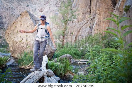 Young woman crossing a creek