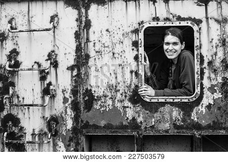 Portrait of a young woman in an industrial container window. Abandoned.
