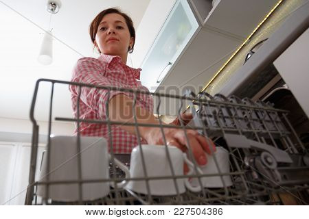 Middle-aged Woman Places Dishes In The Dishwasher