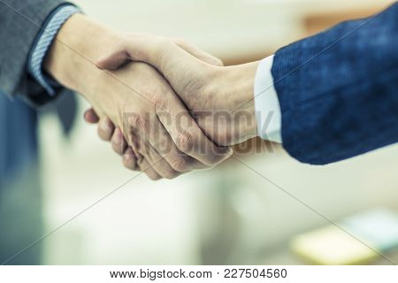 Handshake Of Business Partners On Blurred Light Background.the Photo Has A Empty Space For Your Text