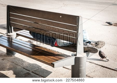 Poor Homeless Man Or Refugee Sleeping On The Wooden Bench On The Urban Street In The City, Social Do