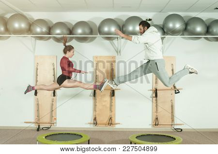 Young Beautiful Fitness Couple Workout Extreme Acrobatic Exercise On Trampoline Jumps As Preparation