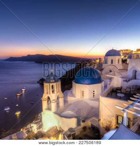 Cityscape Of Oia, Traditional Greek Village With Blue Domes Of Churches, Santorini Island, Greece At