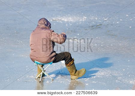 Fisherman With Fishing Rod For Ice Fishing On The Ice Of The Lake