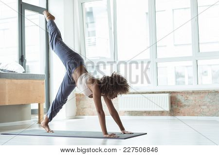 Full Length Side View Serene Woman Taking Exercise On Mat At Home. Copy Space