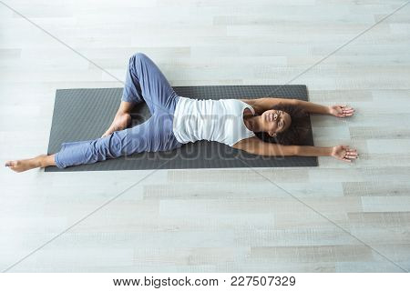 Top View Full Length Calm African Female Lying On Mat In Room. Sport Concept. Copy Space
