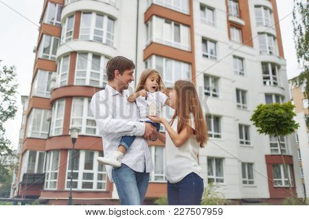 Low Angle Shot Of A Young Happy Family Posing In Front Of New Apartment Building. Father And Mother