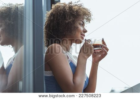 Side View Low Angle Smiling Girl Tasting Mug Of Appetizing Beverage. Copy Space
