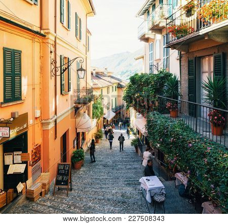 Bellagio, Italy - October 7, 2017: Tourists On Narrow Street With Colorful Houses In Small Town Of B