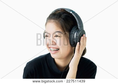 Asian Girl In Black Casual Dress Listening To Music From Black Headphones. In A Comfortable And Good