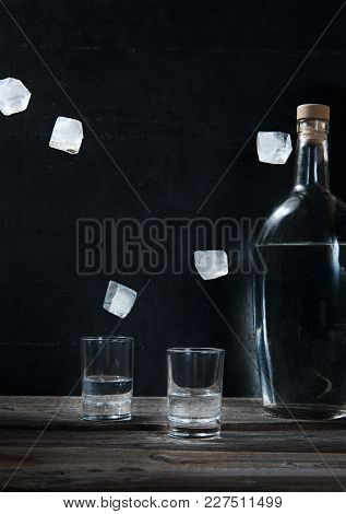 Cold Vodka In Shot Glasses With Flying Levitating Ice And Bottle On A Black Background