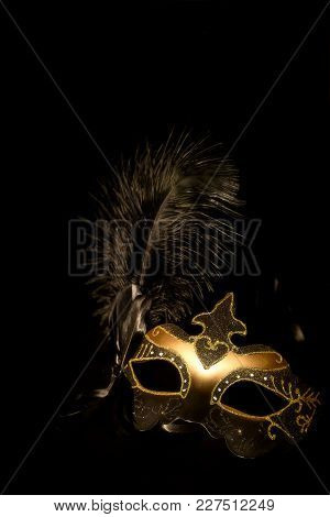 Black With Gold, Theatrical Mask With A Black Feather On A Black Background