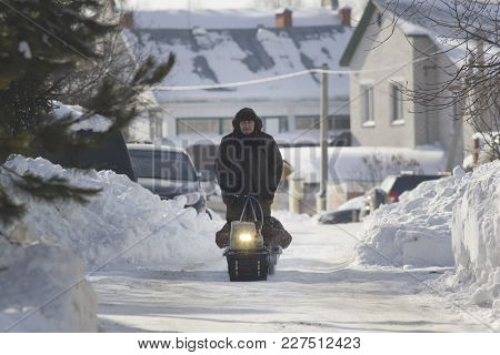 Compact Snowmobile - Motorcycle Towing Pulls Cargo On Snow Countryside, Telephoto Shot