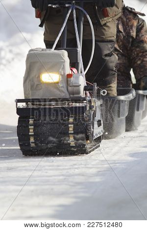 Compact Snowmobile Close Up - Motorcycle Towing Pulls Cargo On Snow Countryside, Telephoto Shot