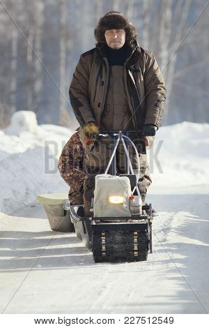Compact Snowmobile For Hunting - Motorcycle Towing Pulls Cargo On Snow Countryside, Telephoto Shot