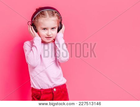 Little girl in headphones over rose background