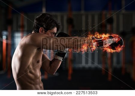 Determined And Confident Boxer With Fiery Boxing Gloves
