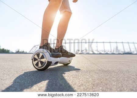 Close Up Man Legs Riding On Gyroscope At Street. Digital Device Concept. Copy Space