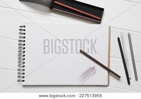 Blank notepad or sketchbook with drawing pencils on wooden table, copyspace, top view