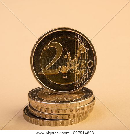 Coin Of Two Euros. Coin On A Blurred Background Coin Denomination Of Two Euros. Currency Of The Euro