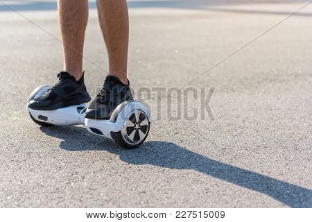 Close Up Young Male Legs Riding On Gyroscope. Technology Concept. Copy Space