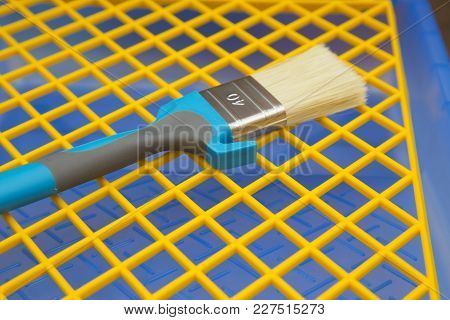 Repair, Redecorating Concept. A Paint Brush On A Blue Plastic Pan With A Yellow Grid, Close Up