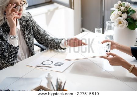 Put Your Signature. Young Girl Is Giving Folder With Document For Senior Elegant Business Woman To S