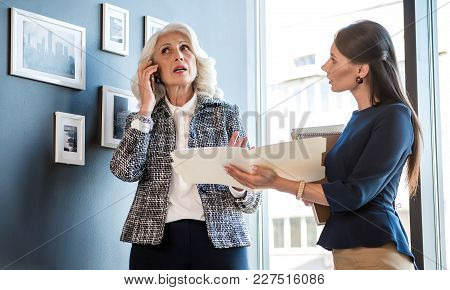 Important Call. Low Angle Of Confident Gray-haired Stylish Woman Is Talking On Mobile Phone While Lo