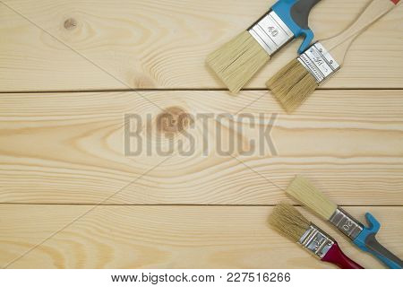Repair, Redecorating Concept. A Set Of Wooden And Plastic New Paint Brushes On A Light Uncolored Woo