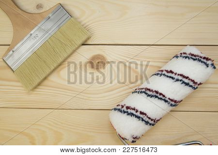 Repair, Redecorating Concept. A Paint Roller And A Brush On A Light Uncolored Wooden Background With