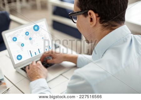 Searching The Net. Dark-haired Well-built Neat Man Wearing Glasses And Working On His Laptop While S