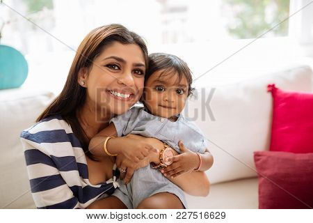 Smiling Happy Indian Woman Hugging Her Baby Girl And Looking At Camera