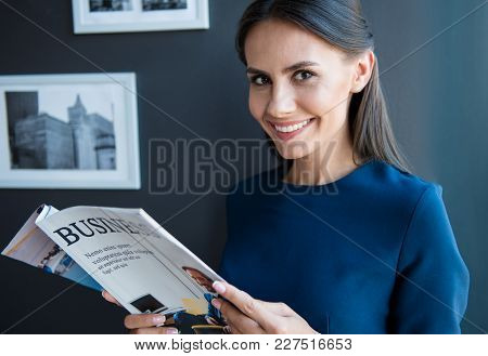 Keep Abreast Of Latest News. Portrait Of Happy Gorgeous Young Woman Is Standing In Office With Open