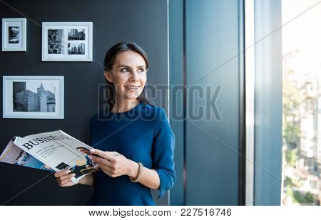Great View. Optimistic Young Gorgeous Young Woman Is Standing In Office With Open Business Journal A