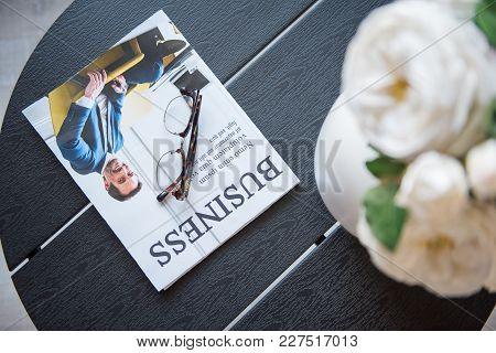 Popular Journal. Close-up Top View Of Black Coffee Table With Glasses, Business Magazine And Vase Wi