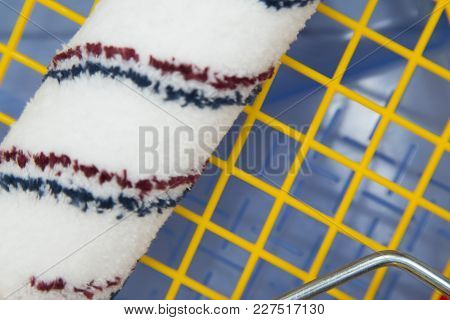 Repair, Redecorating Concept. A Paint Roller On A Blue Plastic Pan With A Yellow Grid, Close Up, Top