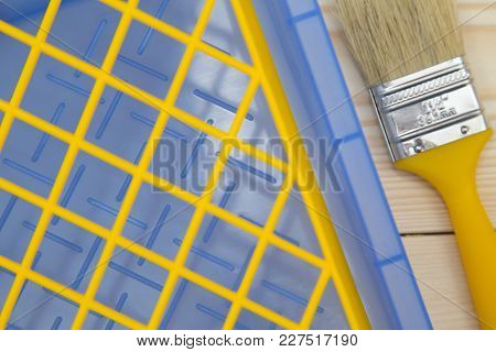 Repair, Redecorating Concept. A Wooden Paint Brush And A Blue Plastic Pan With A Yellow Grid, Close