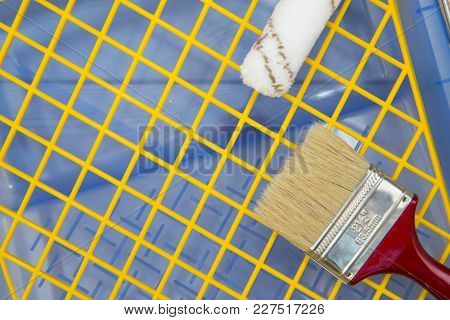 Repair, Redecorating Concept. A Red Paint Brush And A Paint Roller On A Blue Plastic Pan With A Yell