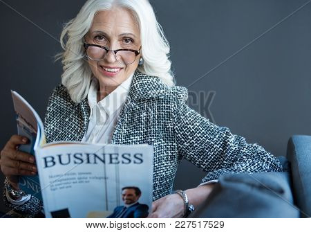 Business News. Portrait Of Optimistic Charming Gray-haired Senior Lady In Glasses Is Sitting On Sofa