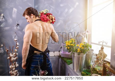Photo Of Attractive Caucasion Male Standing Back To The Camera, Holding Bouquet Of Flowers