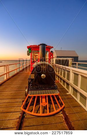 Front View Of Steam Vintage Train On Jetty Of Busselton Town In Western Australia At Sunset Light. S