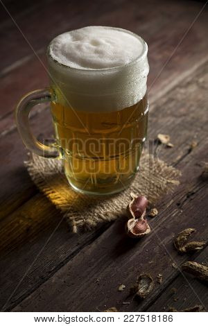 Mug Of Light Beer With Foam Placed On A Burlap Cover And Some Peanuts On A Rustic Wooden Pub Table.
