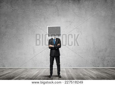 Businessman In Suit With Monitor Instead Of Head Keeping Arms Crossed While Standing Inside Empty Ro