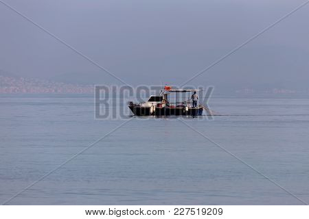The Fisherman Catches Fish In The Open Sea On An Old Fishing Boat On A Cloudy Day