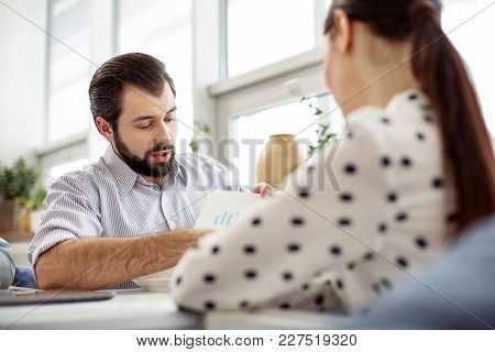 Showing Results. Handsome Concentrated Bearded Man Holding A Sheet Of Paper And Showing A Diagram To