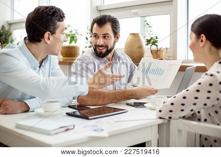 Our Income. Good-looking Cheerful Bearded Man Holding A Sheet Of Paper And Showing A Diagram To His