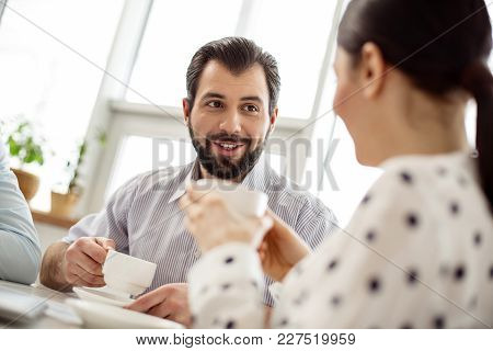 Happy Friends. Handsome Exuberant Bearded Man Drinking Coffee And Smiling And Talking With His Femal
