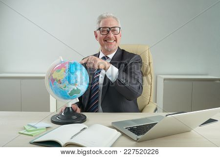 Happy Aged Businessman In Glasses Pointing At Some Country On Globe