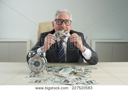 Pensive Aged Businessman Eating Money On His Table