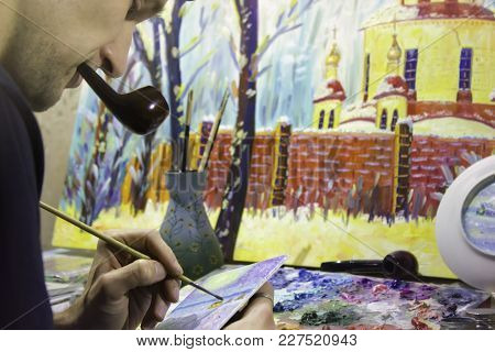 Artist At Work, Painting Oil Painting In The Studio And Smoking Pipe. View With Hand, Brush And Pale